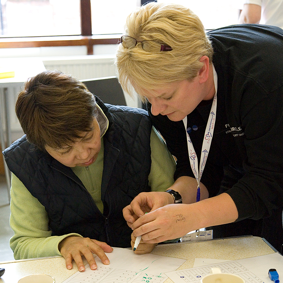 A stroke survivor receiving help in writing.