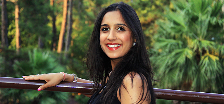 Alisha in a forest-like area, leaning on a railing and smiling while she looks at the camera.