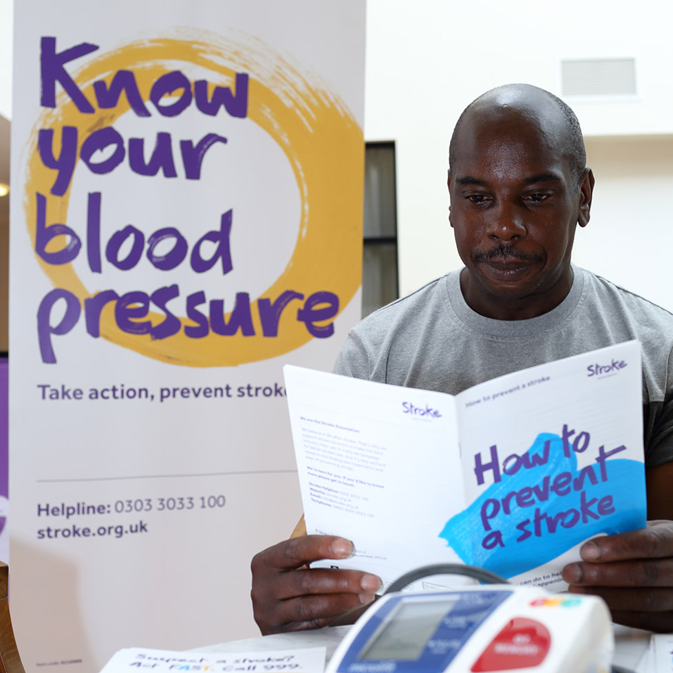 man reading a leaflet about blood pressure and stroke