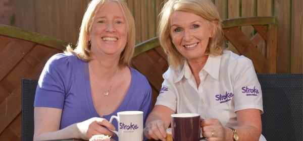 A carer and stroke survivor sat with a tea in a sunny garden
