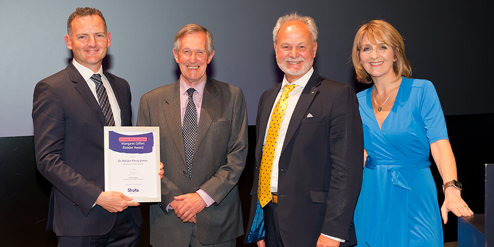 Dr Adrian Parry-Jones holding the award plaque, standing next to John Butt, Barry Rogers, and Kaye Adams.