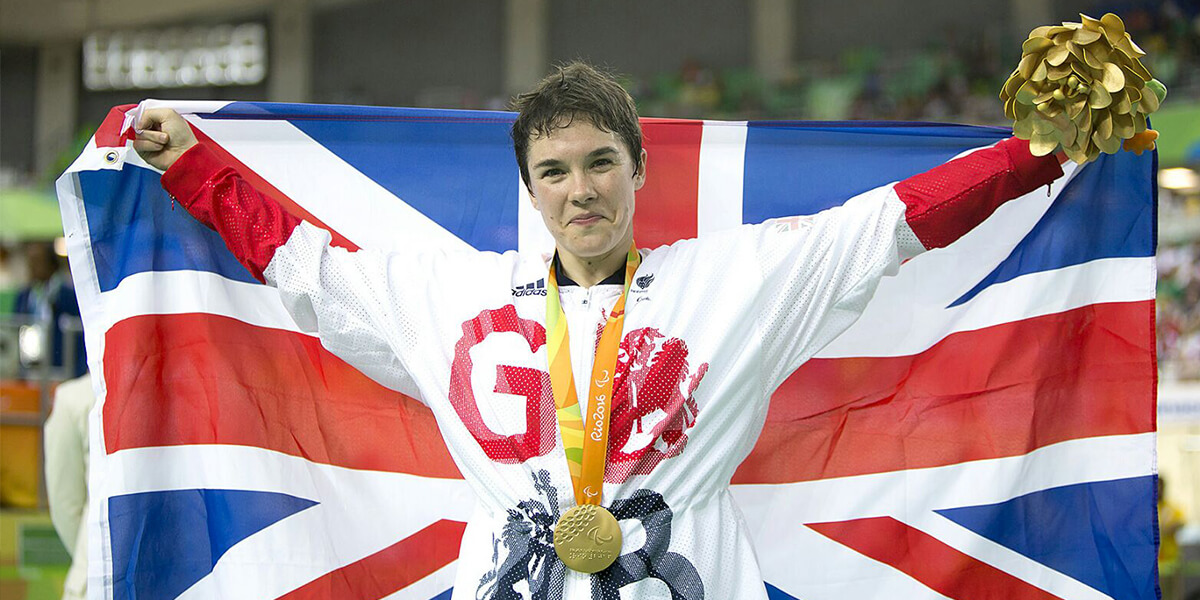 Megan Giglia MBE, Great Britain Gold Medallist, holding UK flag and wearing medal