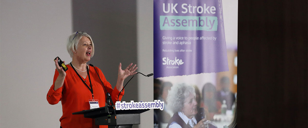 Speaker at UKSA 2019, talking with her hands up, on a podium that says #strokeassembly on it