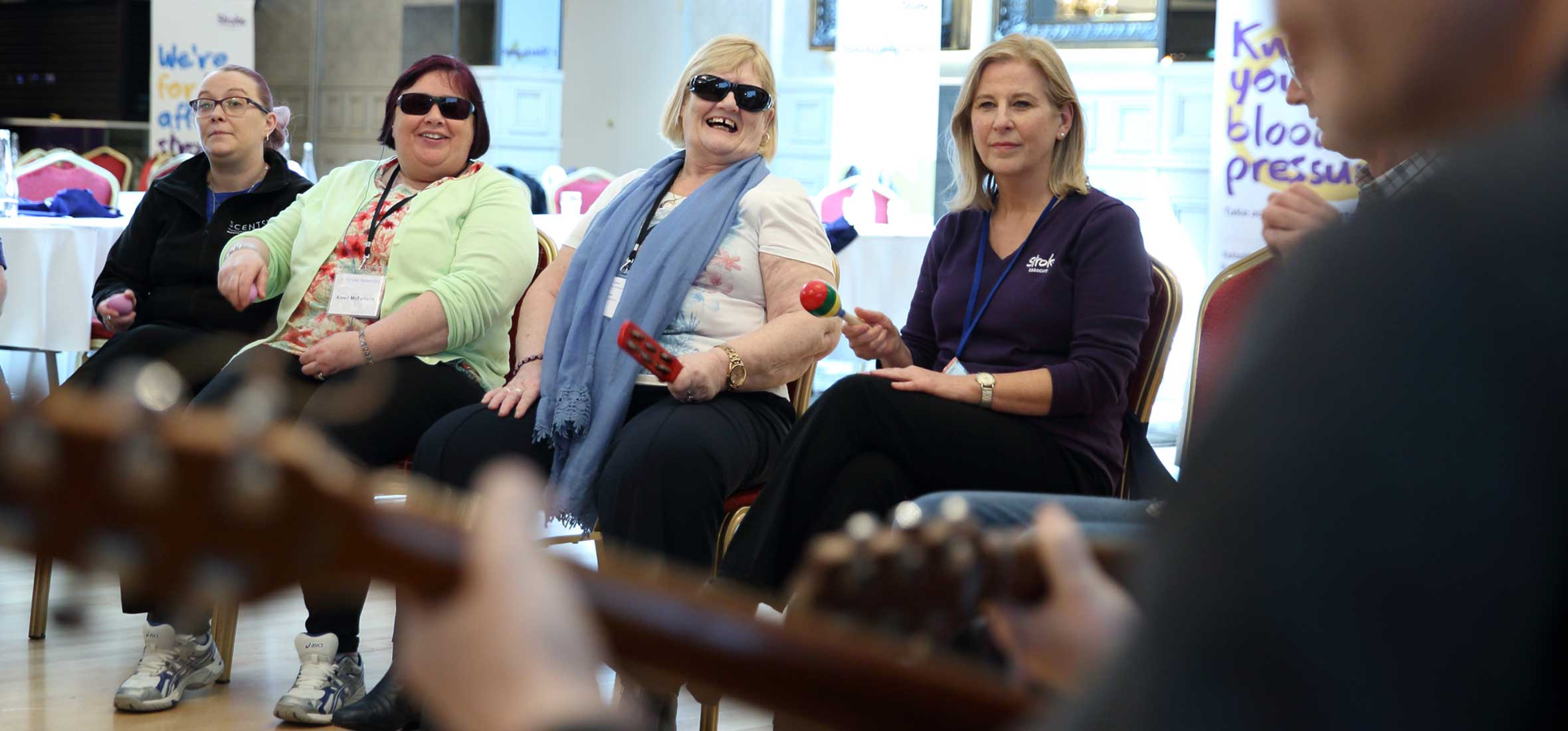 Photos of Stroke Survivors with Stroke Association's team members entertained by a  musician at the UK Stroke Assembly Northern Ireland
