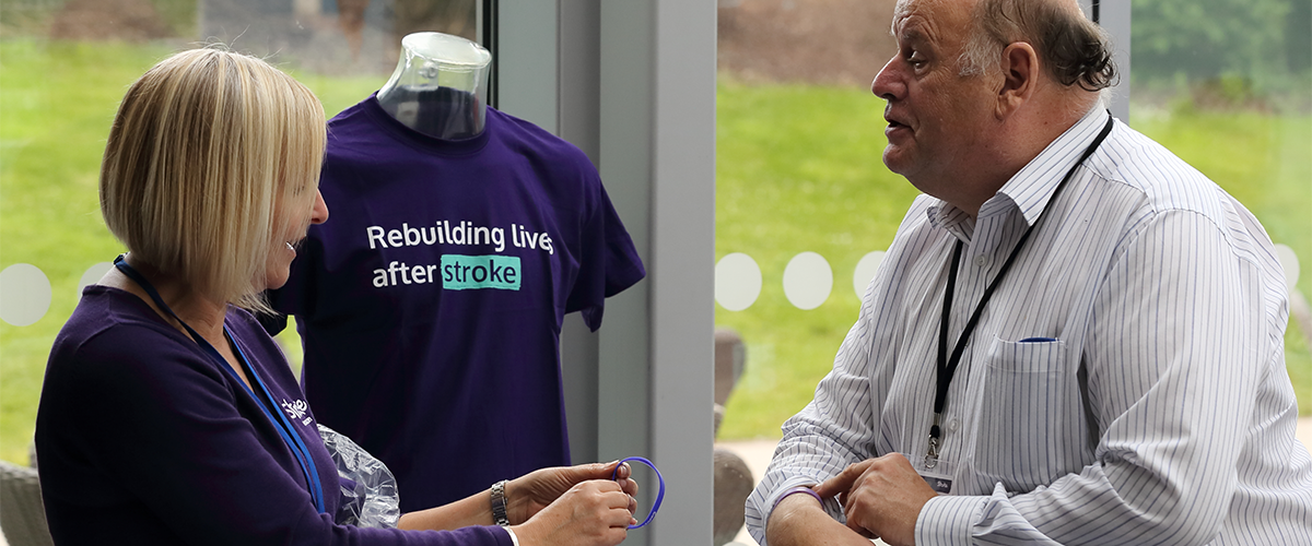 Woman giving a Stroke Association wristband to a male attendee of a conference