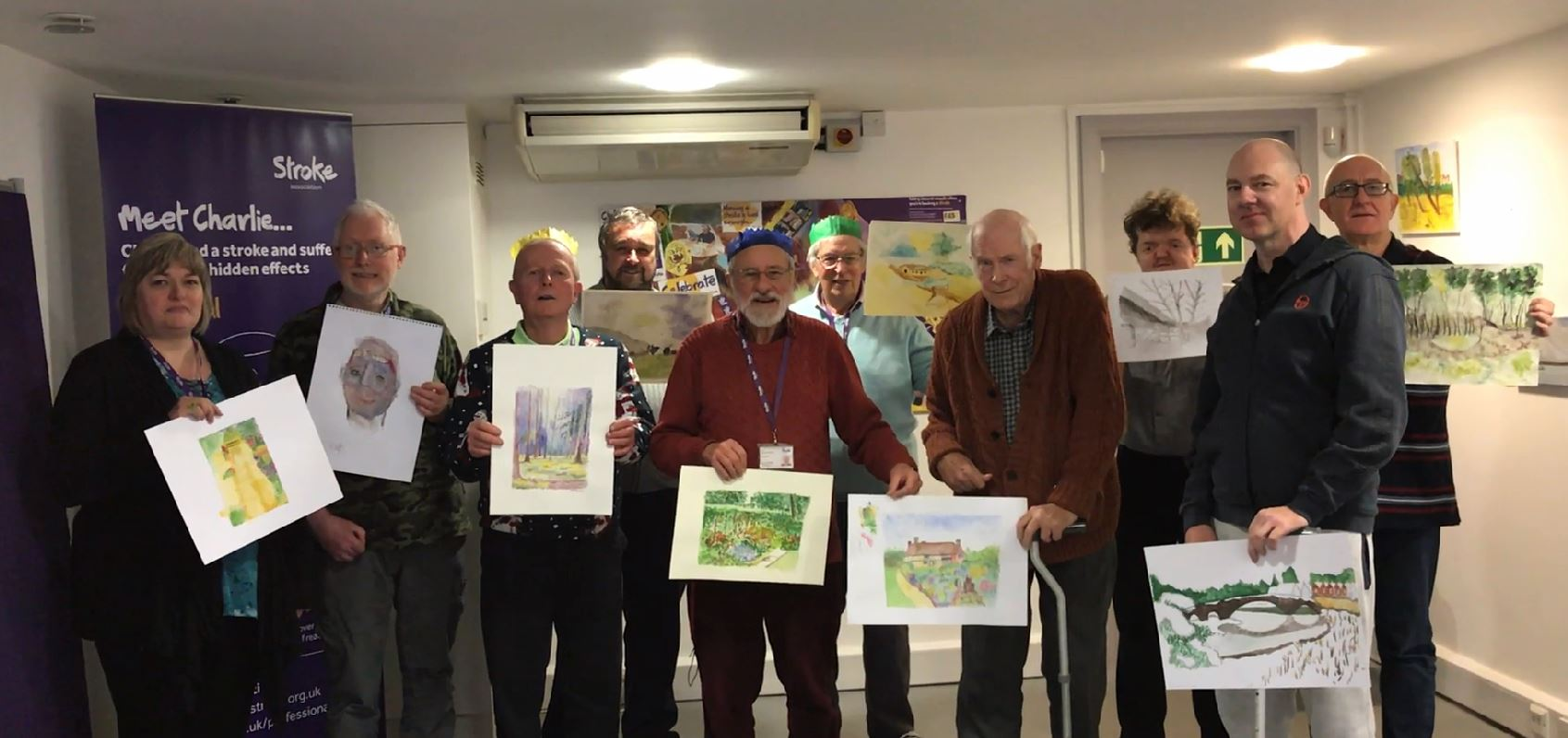 Group of people in a room, each holding artistic creations
