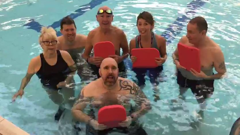 Group of people in a pool, holding red floatation devices