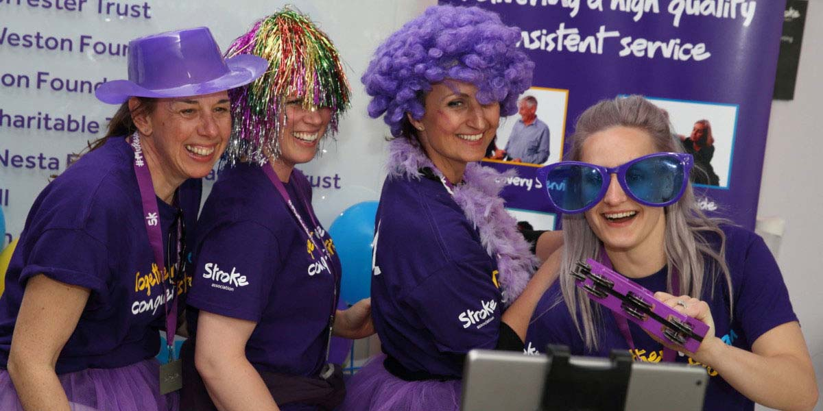 Group of women at a fundraising event, wearing purple Stroke Association clothes and props