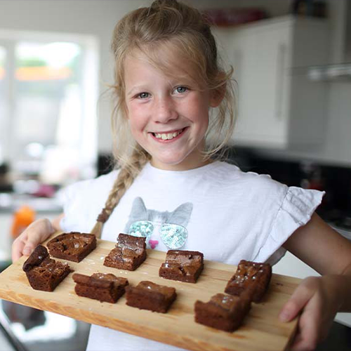 Beth smiling while holding a tray with brownies on it.