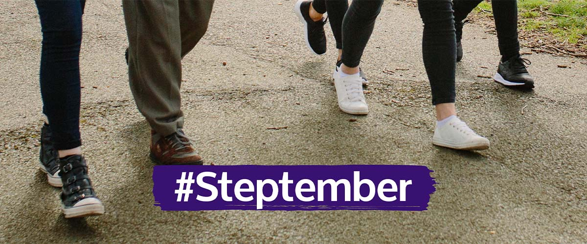 #Steptember banner. Photo of people's legs as they walk, with text overlaid on it.