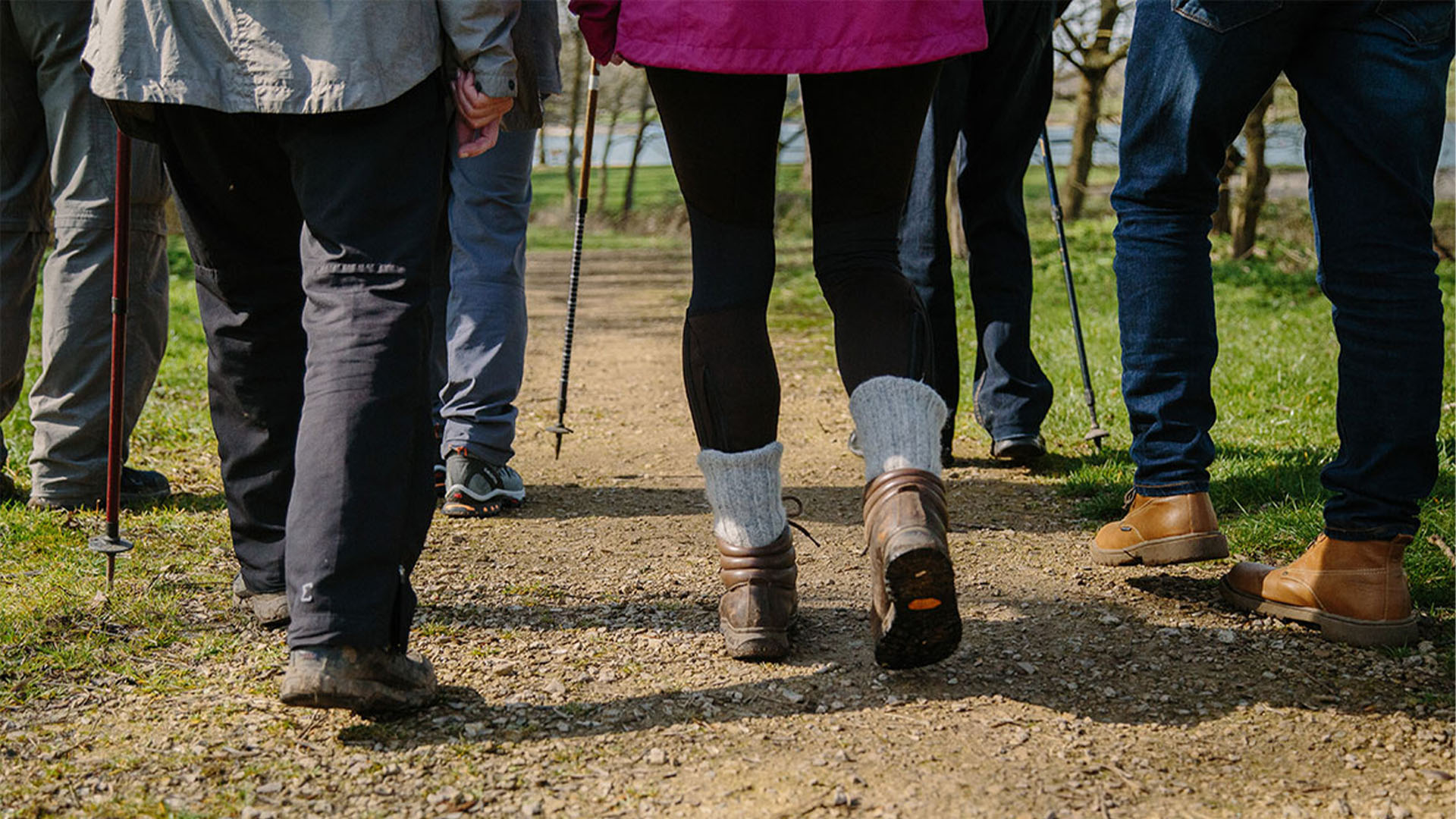 Picture of people's legs, walking with some walking sticks