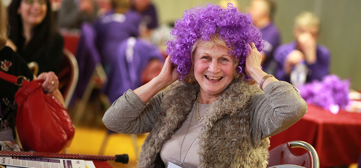 Woman with purpler hair wig, smiling at viewer
