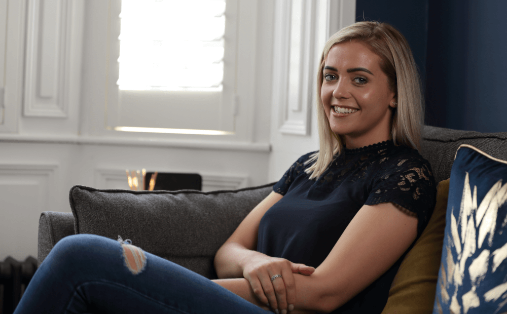 Hannah McGrath, sitting on a couch and smiling at the viewer.