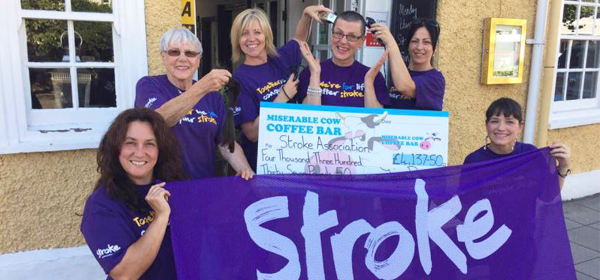 Several people wearing purple Stroke Association shirts standing together and holding a Stroke Association flag. One person is holding a large certificate.