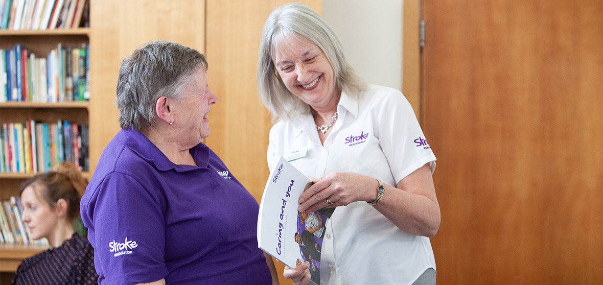 Two women in Stroke Association tops are standing together. Both are smiling