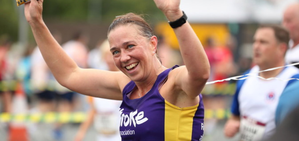 A runner in a Stroke Association vest smiles as she finishes her race