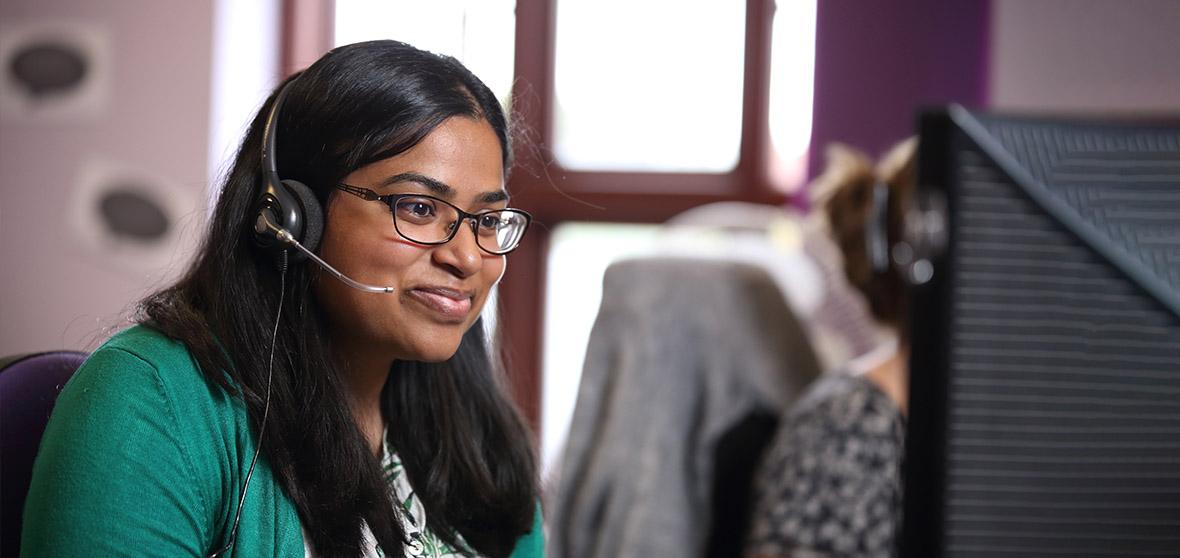 A Stroke Association Helpline Information Officer sits at her computer, smiling