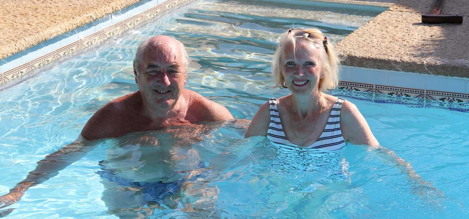 Photo of stroke-survivor Tristan swimming in a pool with his wife