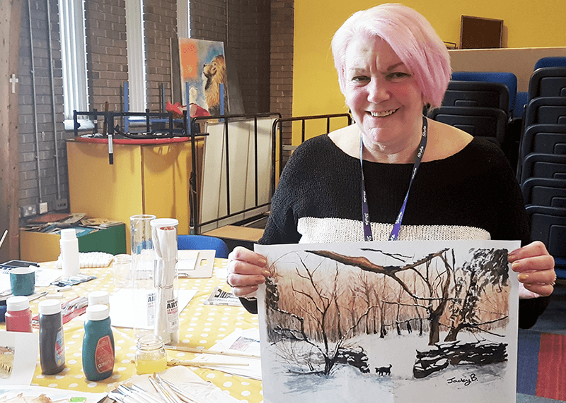 Jacky Baldwin holding her winter-scene artwork for the Stroke Association's Christmas card competition