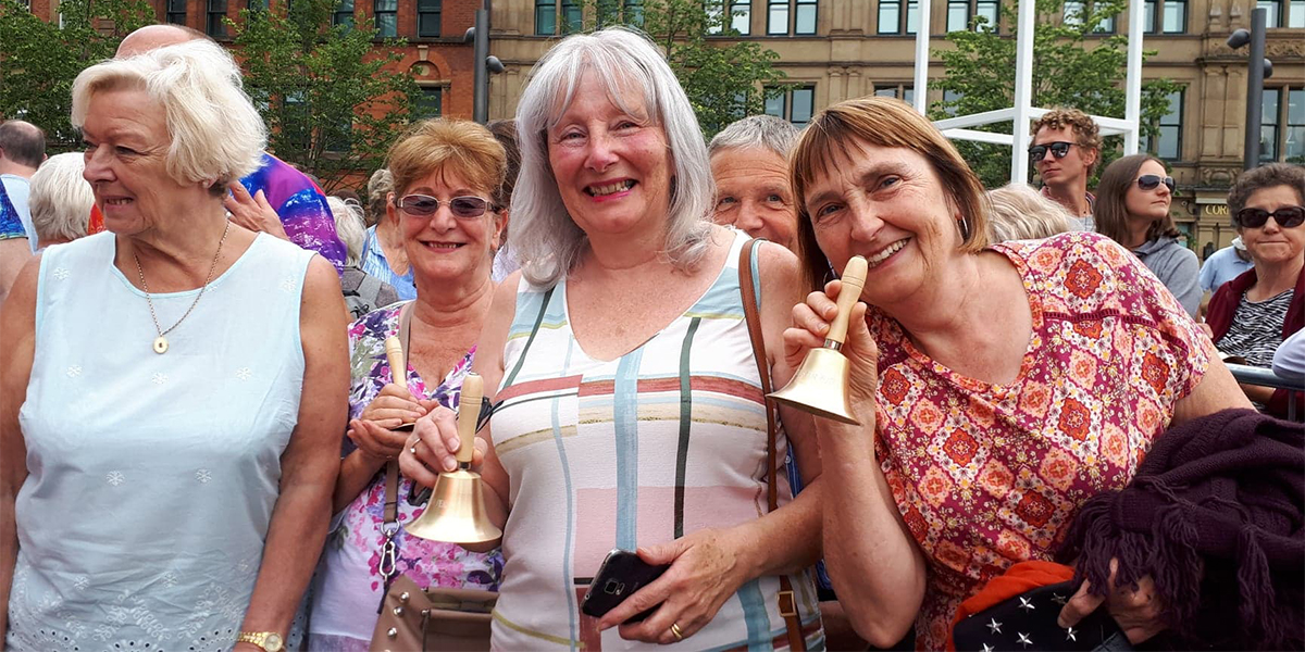 Women holding bells, smiling. At Bells for Peace event.
