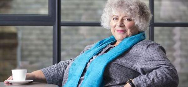 Miriam Margolyes sitting down with a tea cup on a table