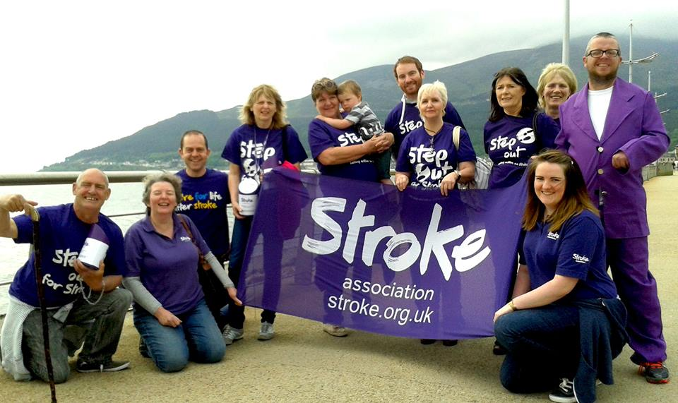 The Newcastle support group posing for a photo near a railing overlooking the sea. The large group of people are all wearing 'Step out for stroke' shirts or purple clothing in general.