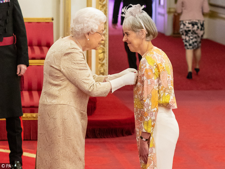 Image of Juliet Bouverie receiving the OBE from Her Majesty The Queen
