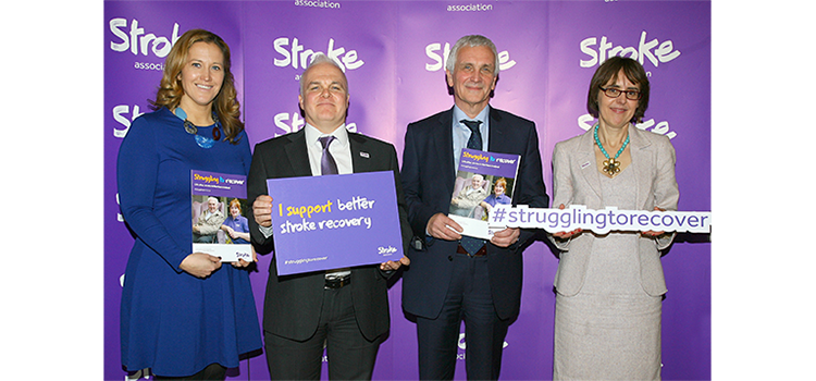 Group including Juliet Bouverie holding Stroke Association booklets, Juliet specifically holding a sign which says: #strugglingtorecover