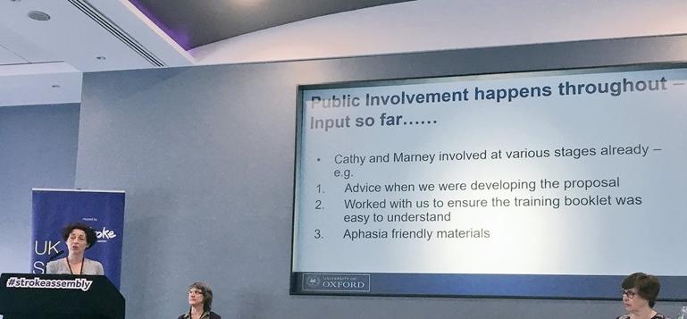 Dr Lisa Hinton giving a presentation at a podium