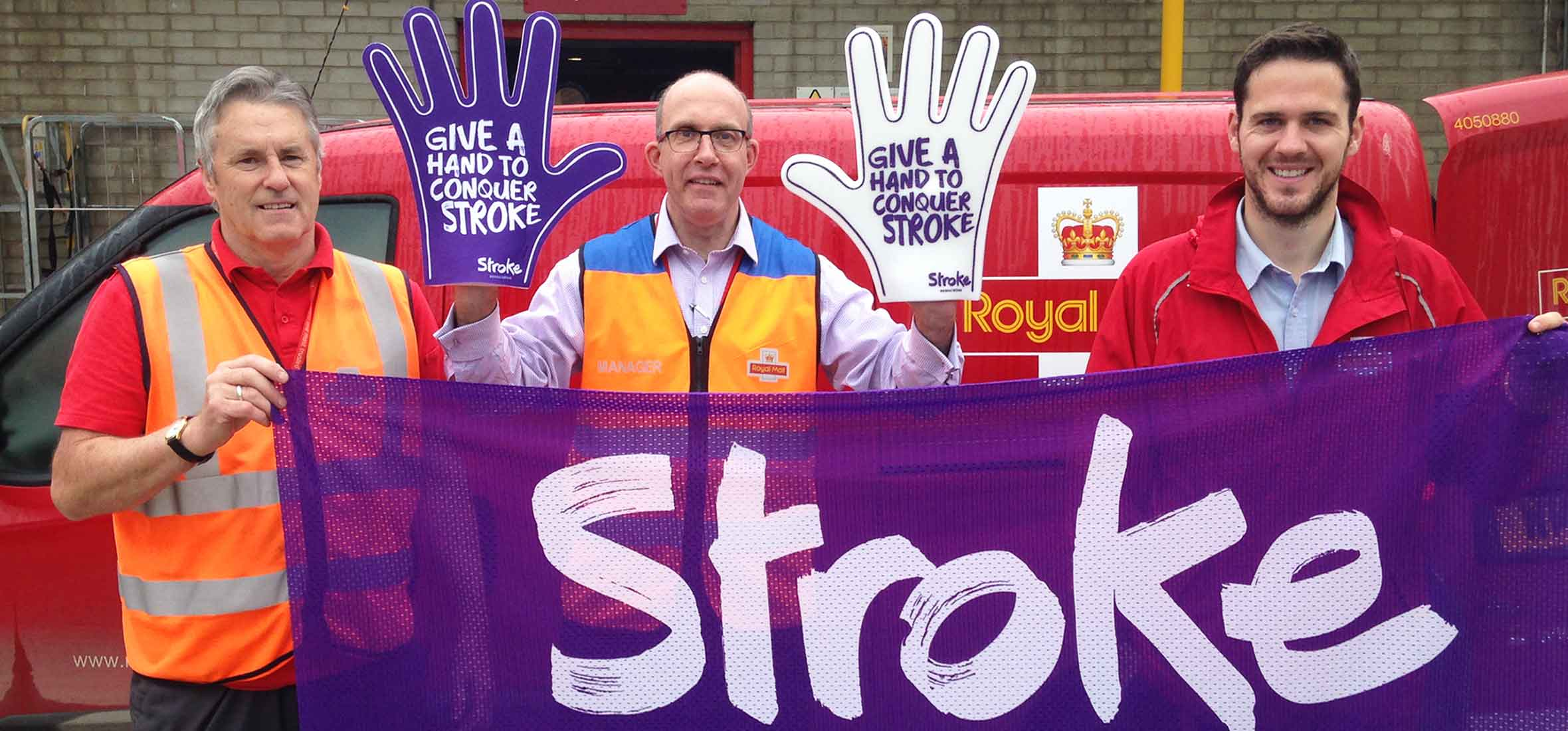 Royal May's workers holding the Stroke Association's purple flag