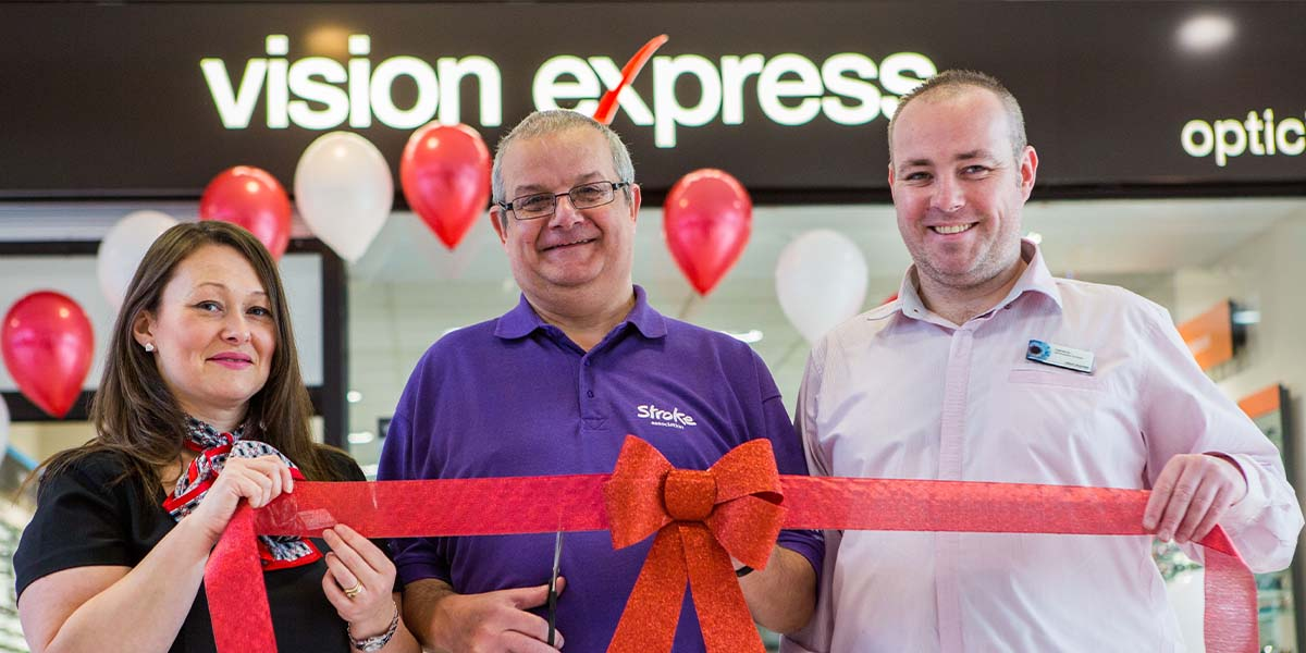 Vision Express corporate partner - 3 people holding red ribbon