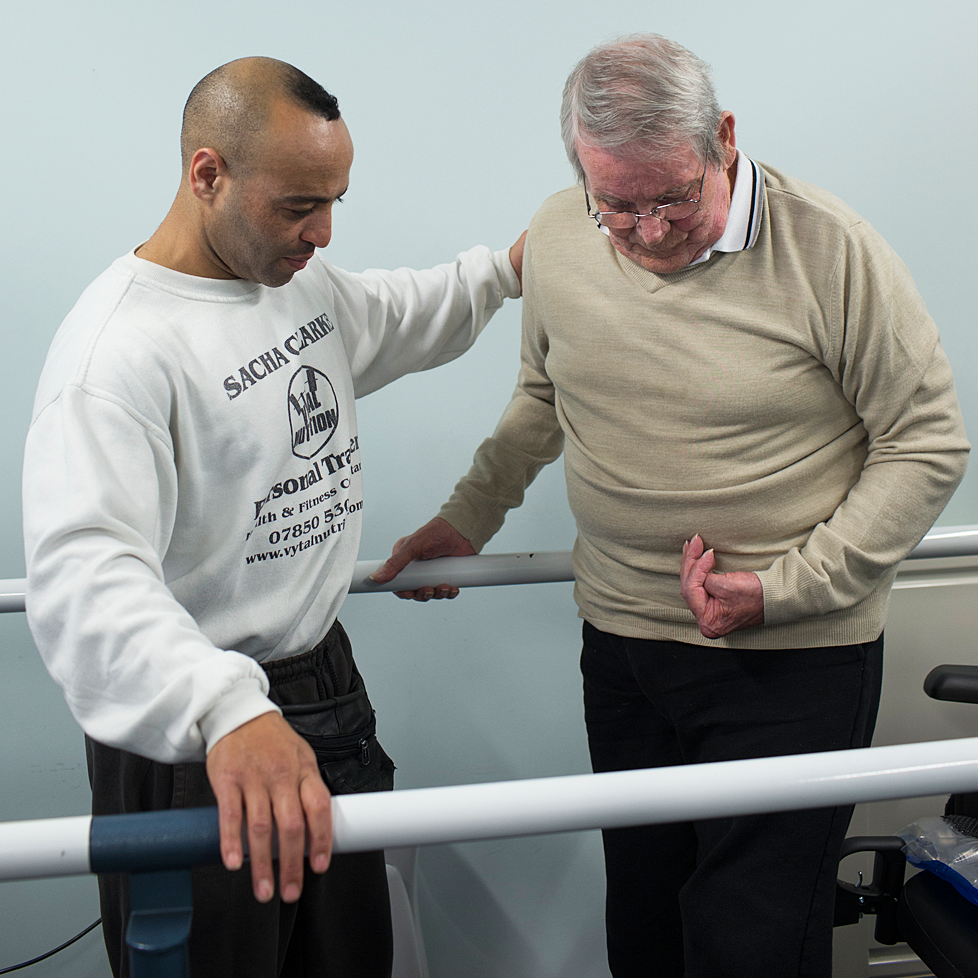 A coordinator helping a stroke survivor with his rehabilitation