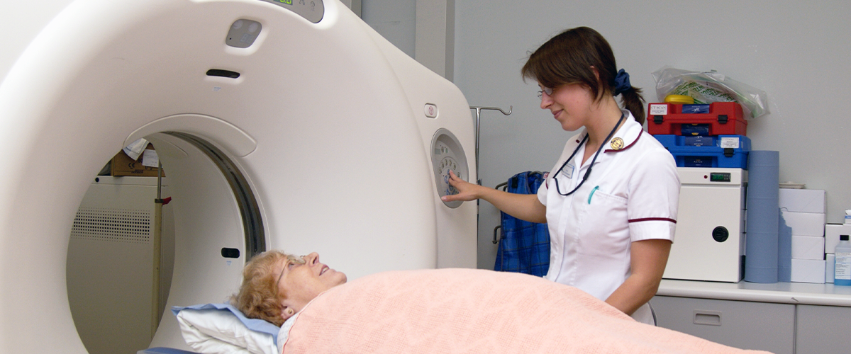 A patient lying down, entering a CT scanner, with a nurse looking over them