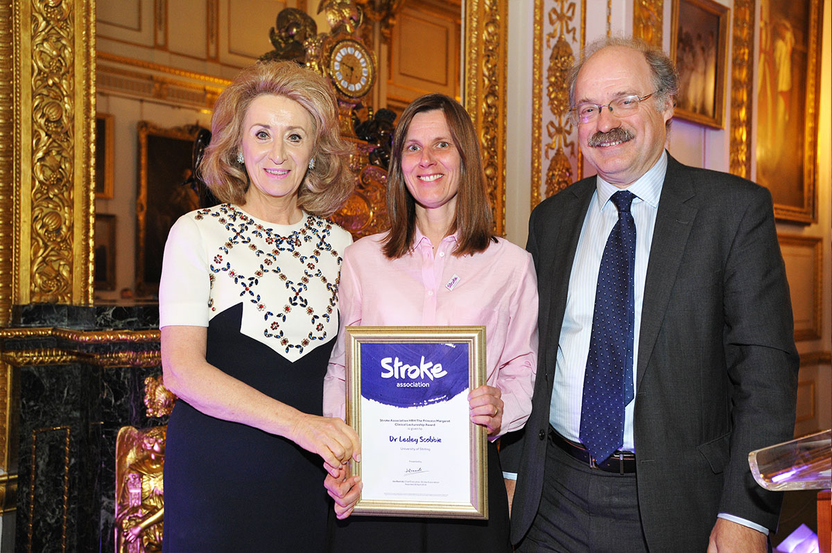 Dr Leslie Scobbie holding her award, standing in between Lady Wolfson and Professor Sir Mark Walport