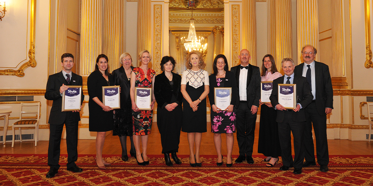 All the award winners standing together, holding their awards, alongside Professor Sir Mark Walport and Lady Estelle Wolfson