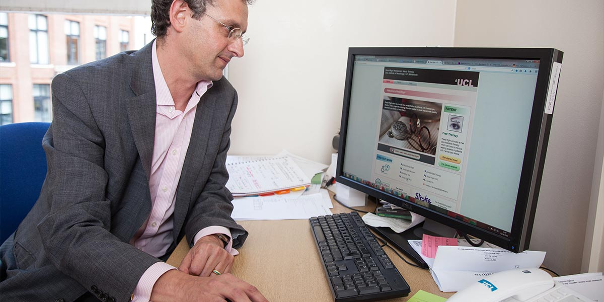 A man in a suit looking a PC screen, his hand on the mouse