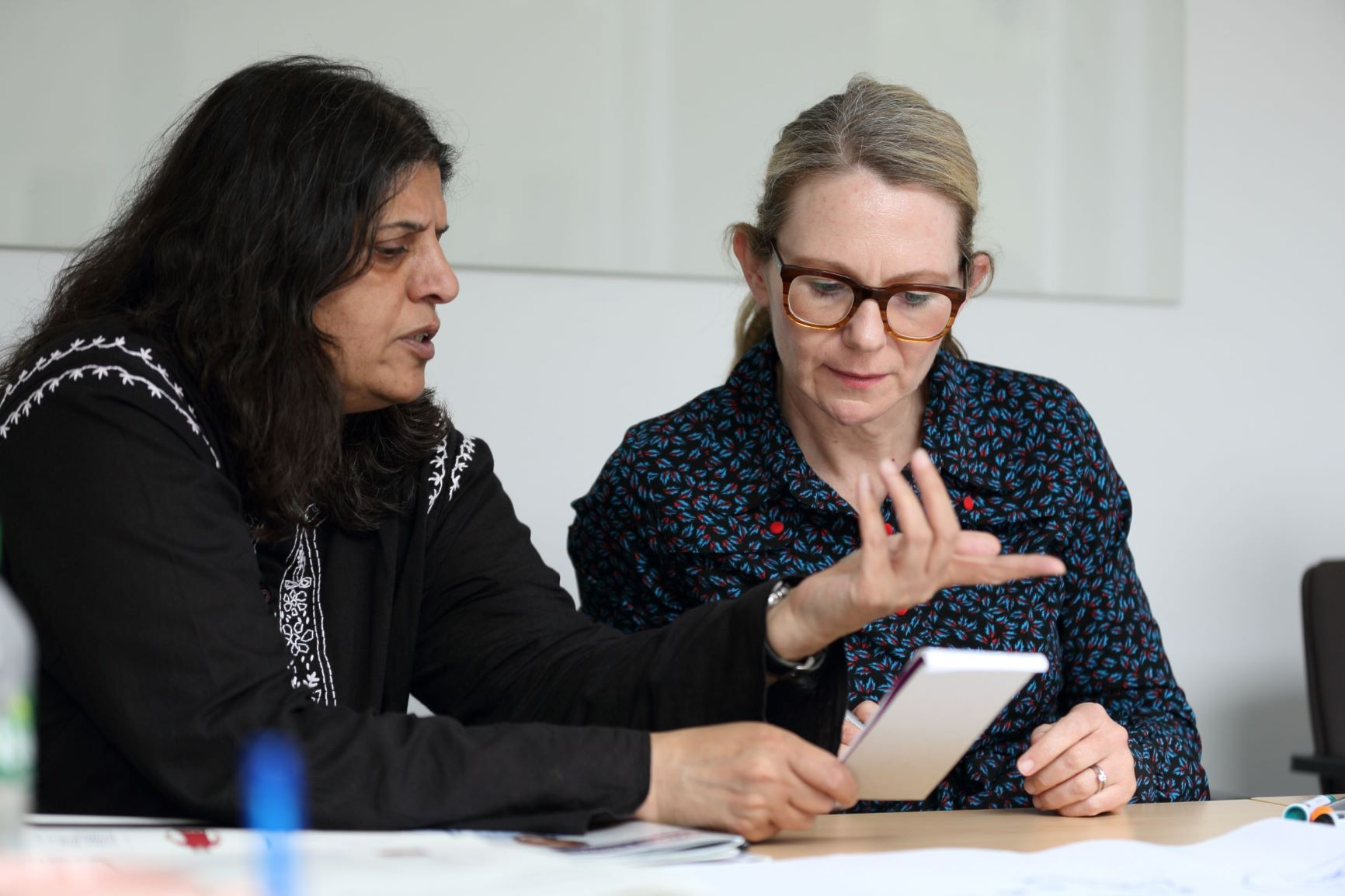 Two women looking at a notepad and having a discussion.