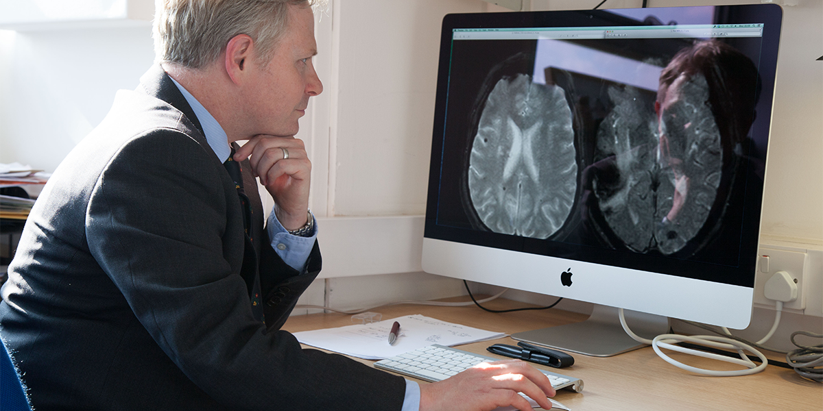 Image of a stroke researcher looking at a brain scan
