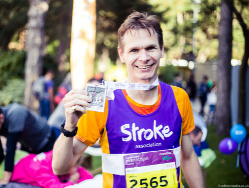Rob running for Team Stroke. He's smiling at the camera and holding something is his right hand.