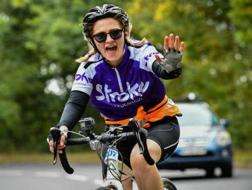 Stroke Association supporter waving while riding bicycle