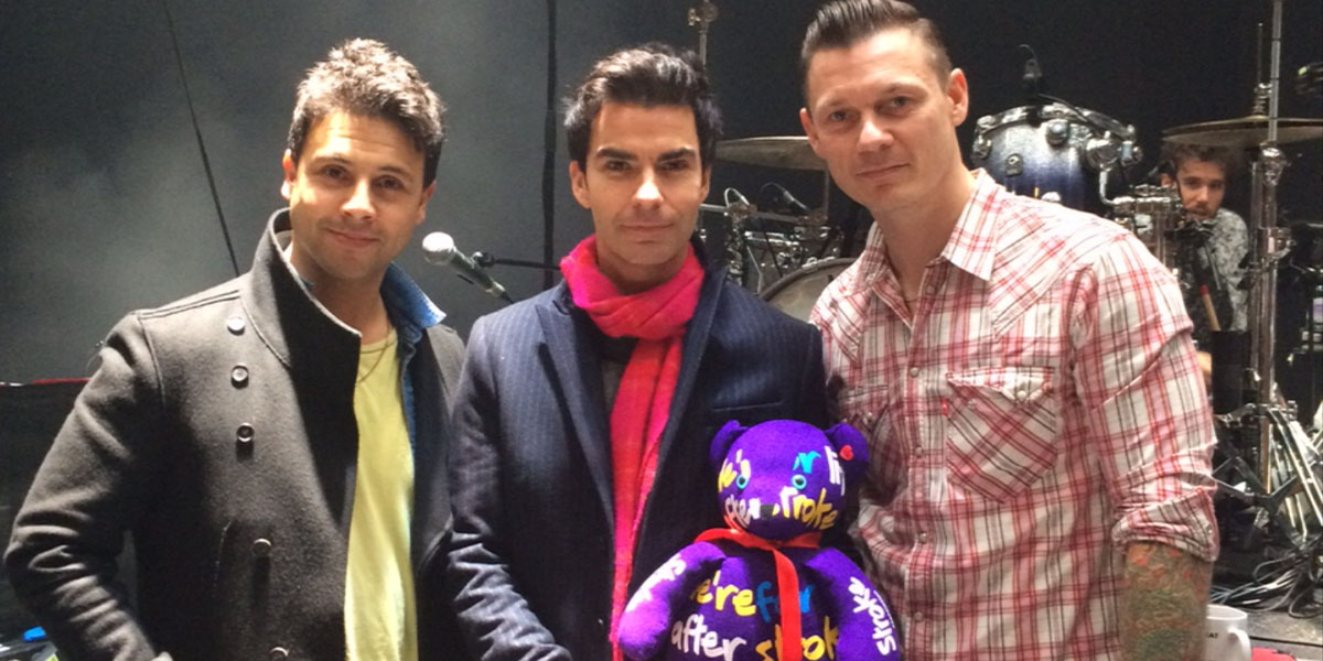 Three men near a stage with a drum kit. The man in the middle is holding a purple Stroke Association teddy bear.