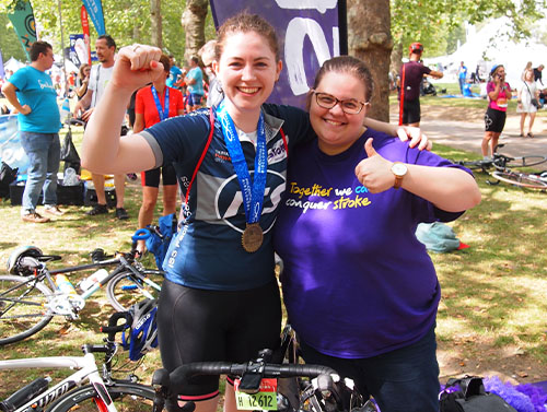 ISS bike rider with a medal doing a fist pump, with her arm around a Stroke Association worker who is doing a thumbs up.