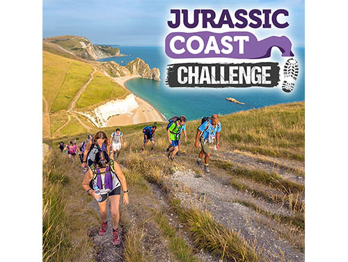 Jurassic Coast Challenge event promotional image. Photo of several people walking up a hill next to a coast.