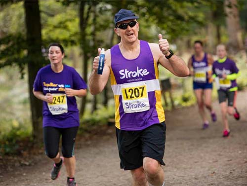 Outdoor runner with Stroke Association top, giving two thumbs up