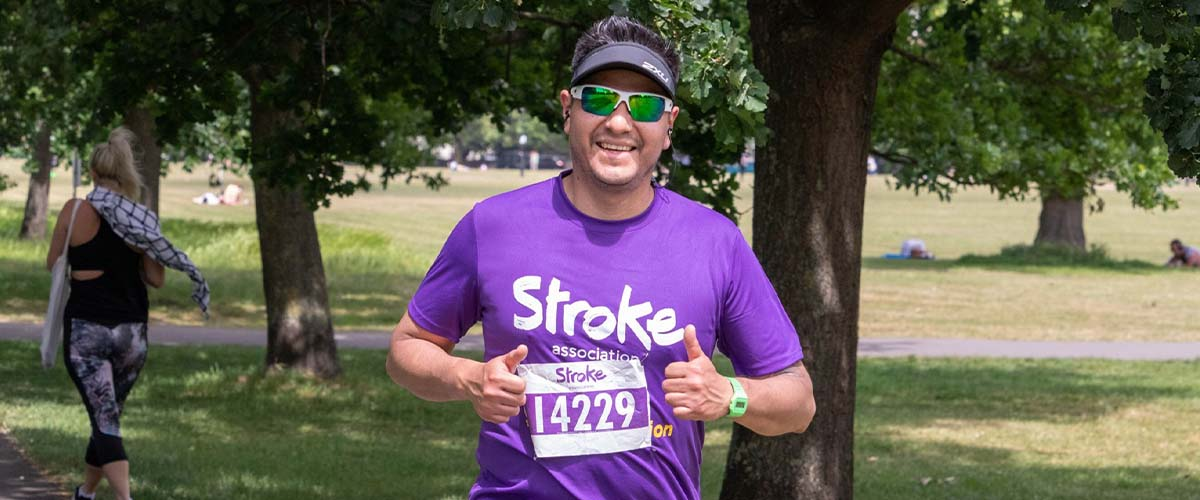 Runner wearing sunglasses and giving two thumbs up
