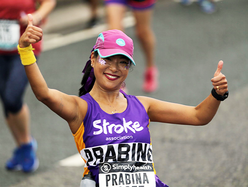 Runner with Stroke Association vest giving two thumbs up
