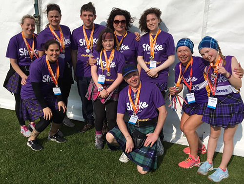 Team Stroke event attendees at Kiltwalk - various men and women standing in a group next to a white tent, each wearing a purple stroke vest and multi-coloured kilts.