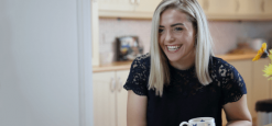 Hannah McGrath in a kitchen, smiling with a mug in her hand.