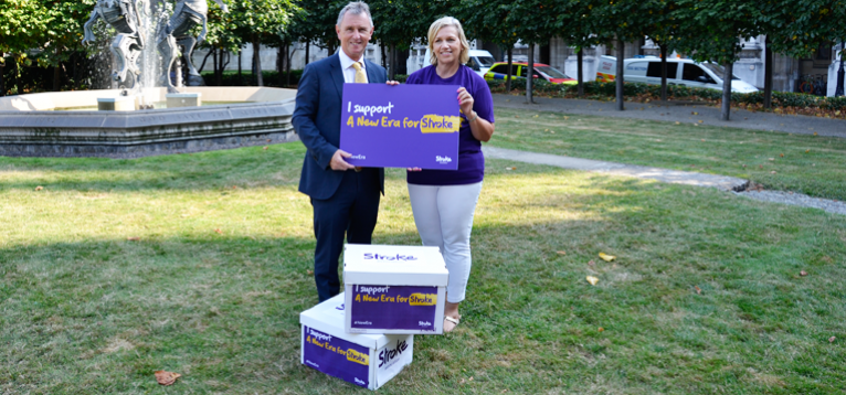 A stroke association representative with an MP holding boxes of signatures for our petition outside parliament