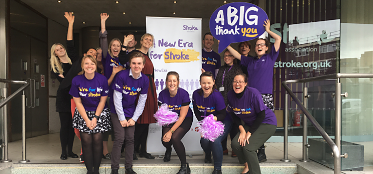 A group of Stroke Association employees dressed in purple, celebrating